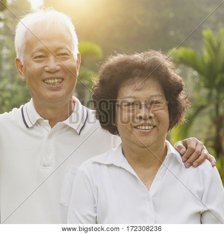 Portrait of healthy Asian seniors retiree couple relaxing at outdoor nature park, morning beautiful sunlight background.