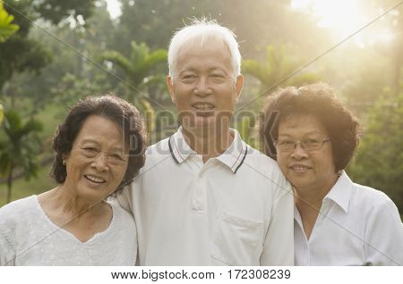 Group of healthy Asian seniors enjoy retired life at outdoor nature park, in morning beautiful sunlight at background.