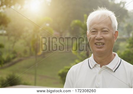 Portrait of healthy Asian senior man at outdoor nature park, morning beautiful sunlight background.
