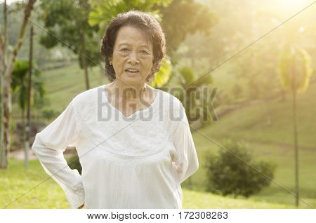 Portrait of healthy happy Asian senior woman doing morning workout at outdoor nature park, beautiful sunlight background.