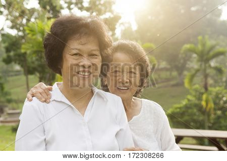 Portrait of healthy Asian seniors mother and daughter sitting at outdoor nature park, morning beautiful sunlight background.