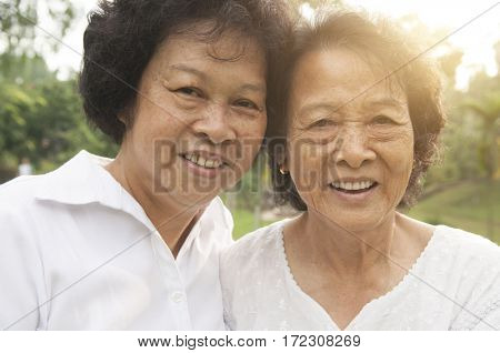 Portrait of healthy happy Asian seniors mother and daughter having fun at outdoor nature park, morning beautiful sunlight background.