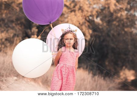 Smiling baby girl 4-5 year old holding big balloons outdoors. Wearing stylish pink dress. Looking at camera. Childhood.
