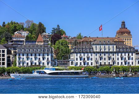 Lucerne, Switzerland - 8 May, 2016: people in boats on Lake Lucerne, buildings on Schweizerhofquai quay in the background. Lucerne is a city in central Switzerland, it is the capital of the Swiss canton of Lucerne.