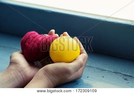 Valentines concept. Close up hand holding red heart and yellow ball on wood with window light. Copy space.