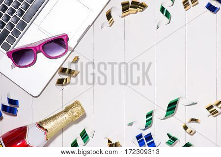 Celebration Flat Lay. Champagne Bottle And Laptop With Copyspace On Wooden Background