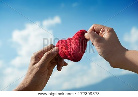 Valentines concept. Close up couple hands holding red heart on blue sky background. Copy space.
