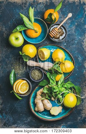 Ingredients for making natural hot drink in blue ceramic plates over dark blue shabby background. Oranges, mint, lemon, ginger, honey and apple, top view. Clean eating, detox, dieting concept