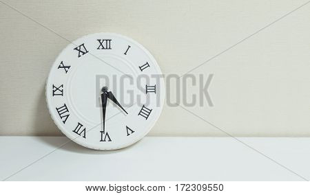 Closeup white clock for decorate show half past four p.m. or 4:30 p.m. on white wood desk and cream wallpaper textured background with copy space