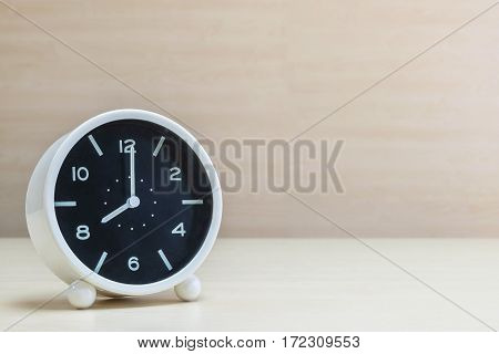 Closeup alarm clock for decorate in 8 o'clock on brown wood desk and wall textured background with copy space