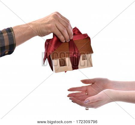 Close-up Of Man Giving Wooden House Model Tied With A Bow To Woman