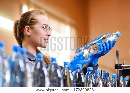 Young happy female worker at factory checking bottles with pure water