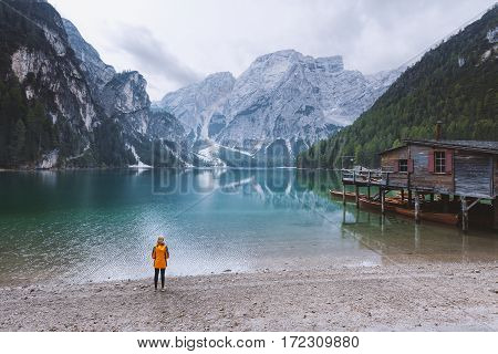 Young woman watching the tranquil morning scene at lake Braies - Dolomites mountain range Italy.