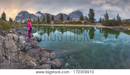 Young woman watching the tranquil sunset scene at lake Limedes - Dolomites mountain range Italy.