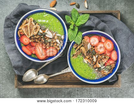 Healthy breakfast. Green smoothie bowls with strawberries, granola, chia and pumpkin seeds, dried figs and nut in wooden tray over grey concrete background, top view. Diet, clean eating food concept