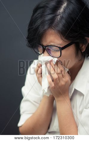 Close up of sad woman with a tissue. Short hair female sneezing. ILLness depression and allergy concept. Asian woman wear eyeglasses sneezing in a tissue.
