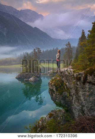 Young woman standing on cliff and watching the peaceful sunrise scene at lake Supperiore di Fusine - Julian mountain range Italy.
