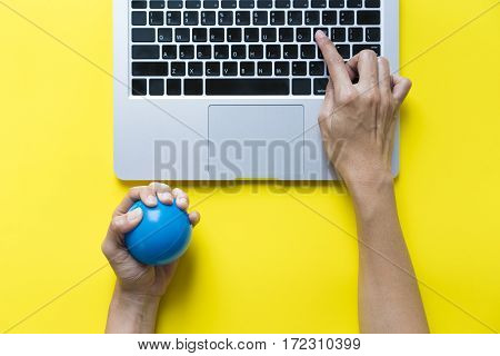 Office worker typing email on computer feels stressed and nervous holds a stress ball in her hand