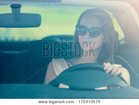 Attractive girl driving car at idyllic summer day.
