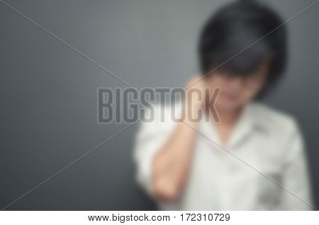 Blurred and de-focused concept Asian young woman pain in neck. Glasses woman be ill and neck pain. Copy space.