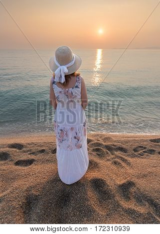 Beautiful girl on the sandy beach watching idyllic sunset by the sea.