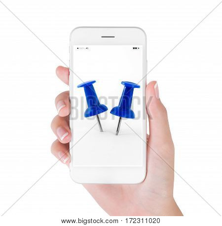 Woman using smart phone searching close up blue push pin object and office supplies concept isolated on white background.