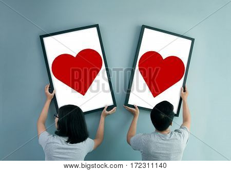 Separated Asian couple concept. Asian couple holding heart in picture frames. Rear view of lover.