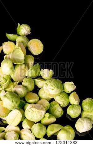 green fresh whole and cut organic Brussels sprouts isolated on black glossy background