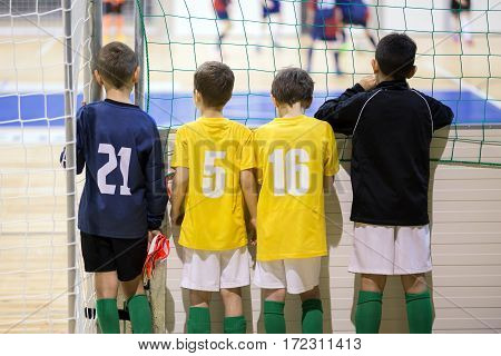 Indoor football soccer match for children. Youth soccer team together watching match. Boys ready to play tournament football futsal match. Soccer football background.