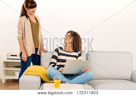 Two beautiful women at home working with a laptop