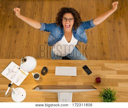 Top view of a happy businesswoman with arms open at the office