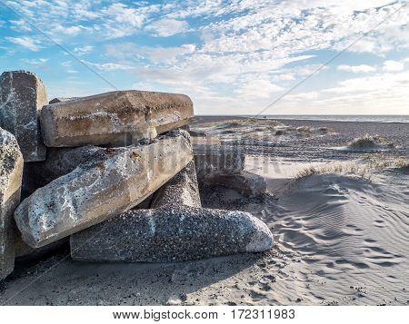 beach with concrete pillars that serve as coastal protection against flooding and sand erosion in storm