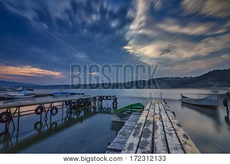 exciting long exposure seascape on harbor with wooden pier and boat