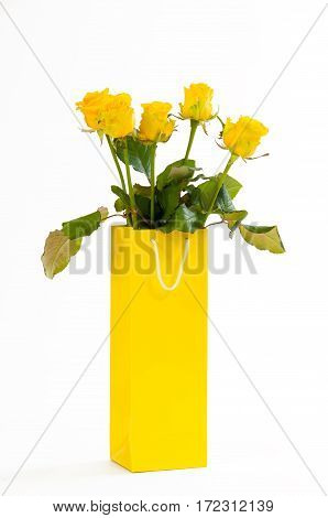 Yellow roses bouquet in a yellow paper bag, isolated on white background