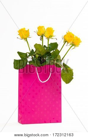 Yellow roses bouquet in a pink paper bag, isolated on white background