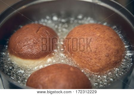 Three Doughnuts Frying In Hot Oil