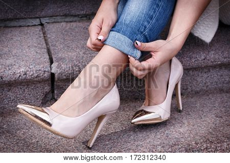 Female Legs In A Beautiful Peach High-heeled Shoes With Gold Nose. Close-up. Hands Corrected Jeans.