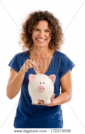 Portrait of a happy middle aged woman puting some money on a Piggybank
