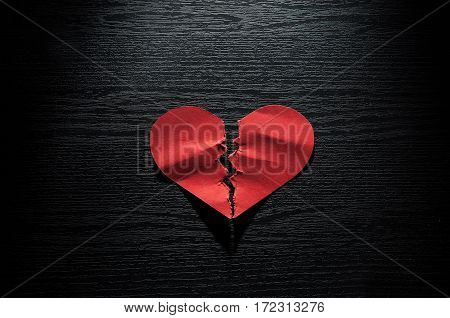 Valentines day with red broken heart concept red crumpled paper on dark wood.