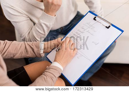 Preliminary diagnosis. Close up of psychologists notes with a preliminary diagnosis while being shown to the patient during the psychological session