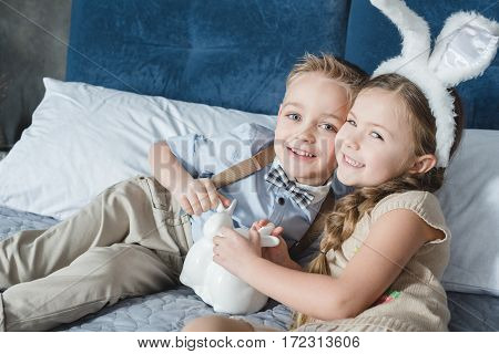 Cute smiling siblings lying on bed with decorative easter bunnies