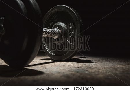In the dark mood, Close up of dumbbell with lighting and shadow on black background. Copy space.