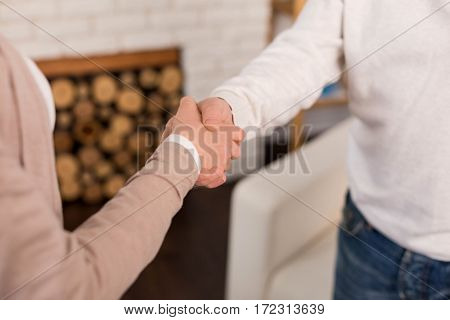 Gretting each other. Close up of a handshake of two people while greeting each other