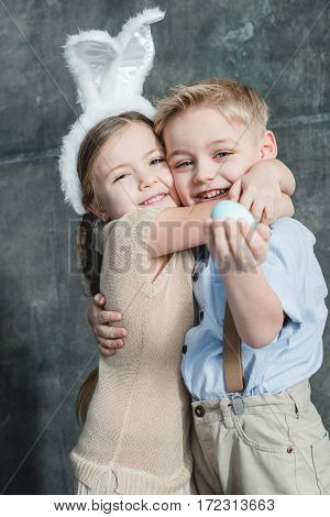Cute smiling kids hugging and holding painted easter egg