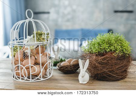 Beautiful easter composition of eggs decorative bunny and green plant