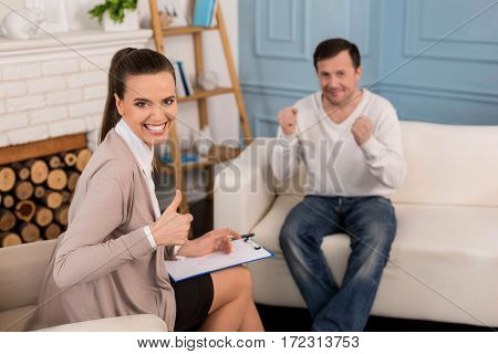 Everything is great. Cheerful positive attractive woman sitting in the armchair and smiling while showing OK sigh