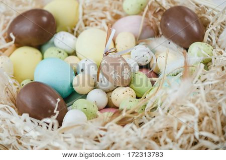 Close-up view of painted and chocolate easter eggs in decorative shavings