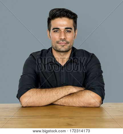 Man sitting arms crossed on table