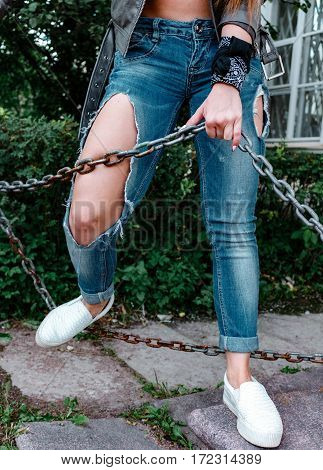 Female Legs In Torn Jeans, Close-up, Girl Holding A Rusty Chain.