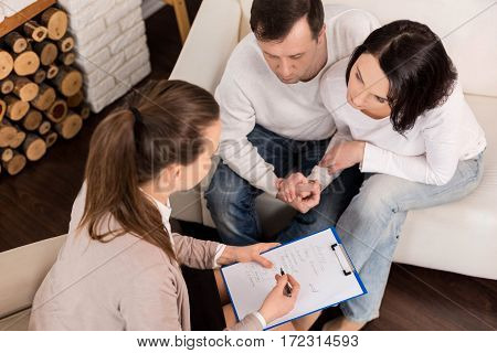 Discussing a problem. Good looking pleasant loving couple holding their hands and looking at the therapists notes while listening to her